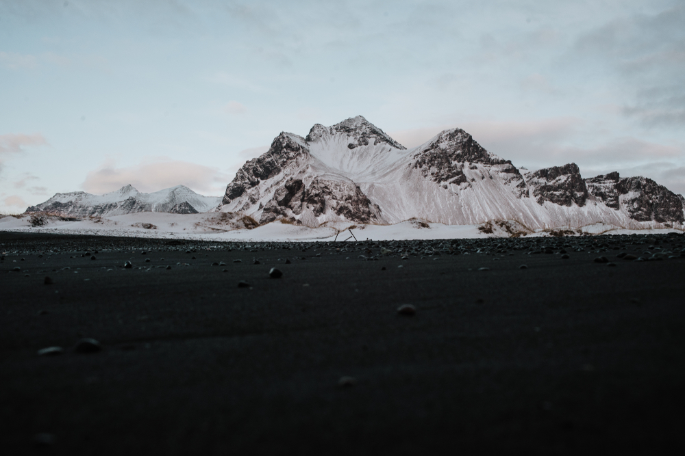 black sand beach with mountain in background