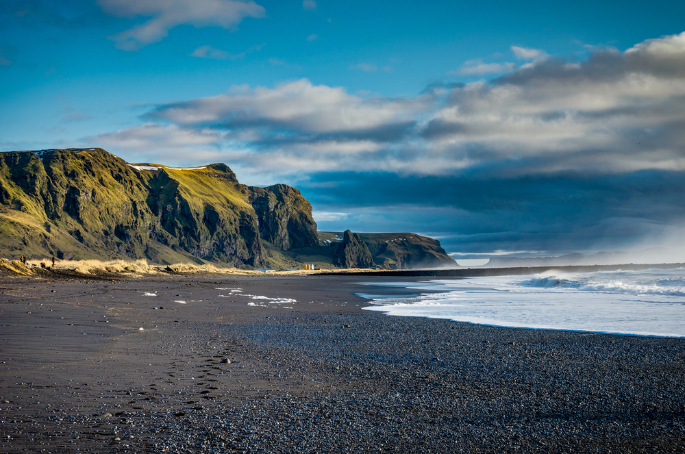 black sand beach in iceland with waves and mountains