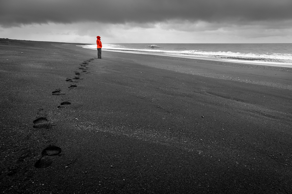 person standing on black sand beach in iceland
