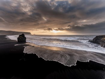 black sand beach in iceland with waves on it at sunset