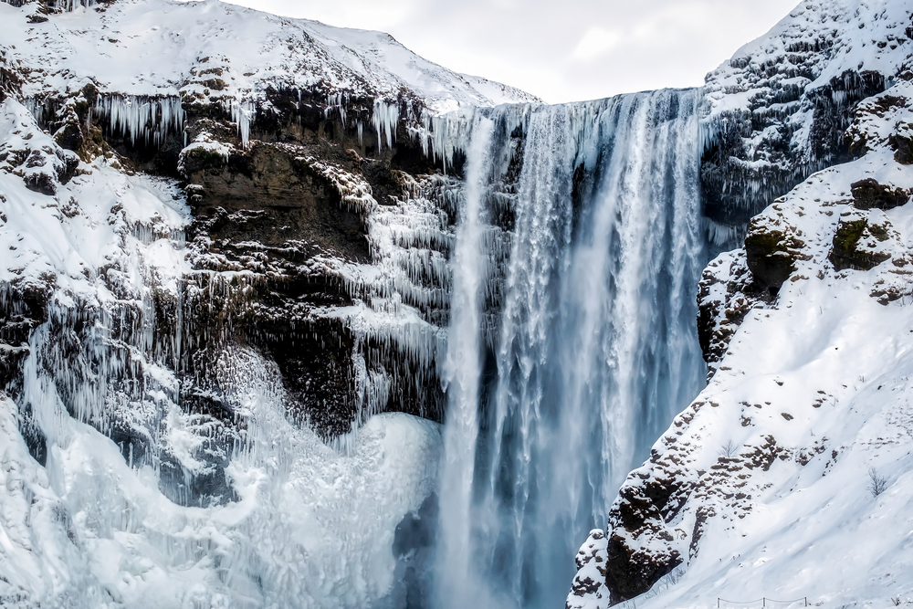 close up of skogafoss waterfall in iceland surrounded by snow on a cloudy winter day