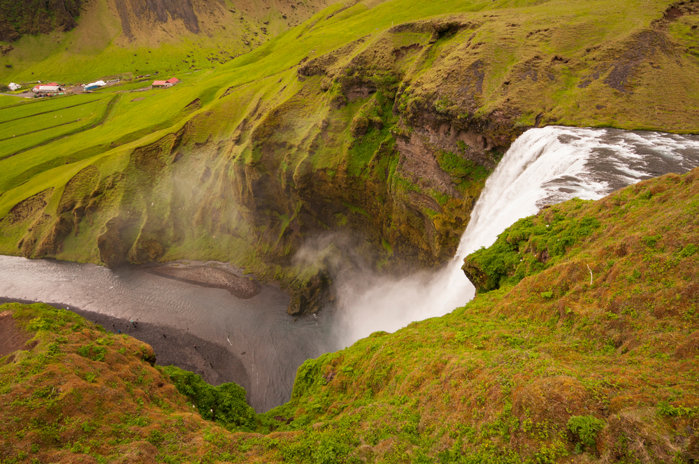 a view from the top of skogafoss waterfall in iceland surrounded by green grass on a nice summer day