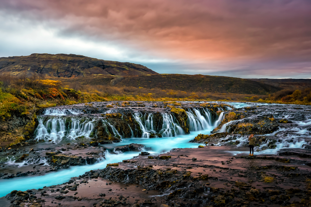 The bright blue water of Bruarfoss against a vivid sunset.