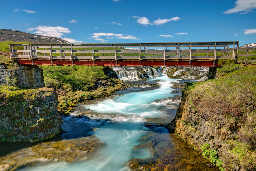 A footbridge over the river in front of Bruarfoss.