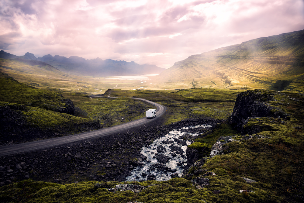 An aerial shot of a campervan in Iceland driving through the mountains.