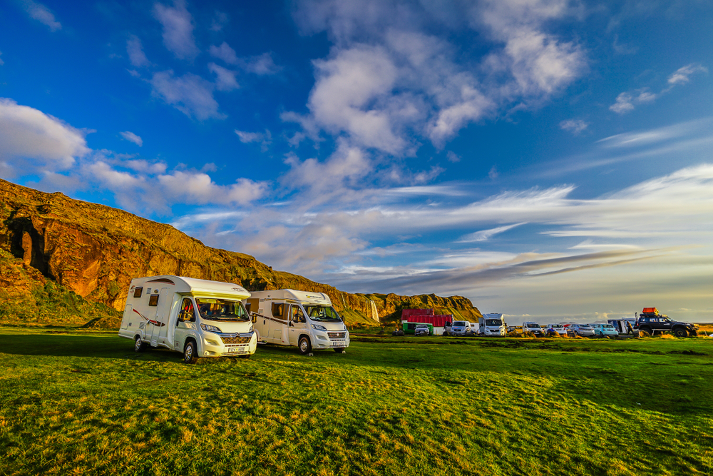 A campsite in Iceland with campervans in an open field.