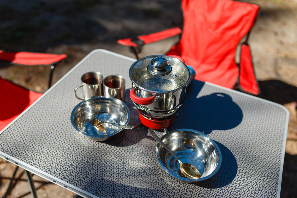 A table with a camp stove and dishes.