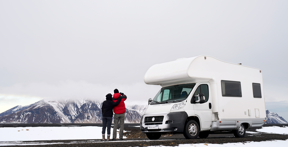 Two people standing next to a motorhome in Iceland in a snowy landscape.