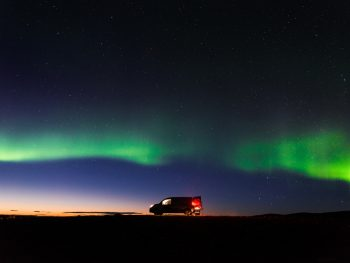 campervan in iceland with the northern lights behind it