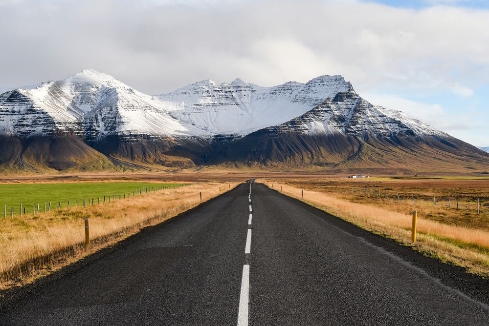 A black, paved road stretching towards snowy mountains.