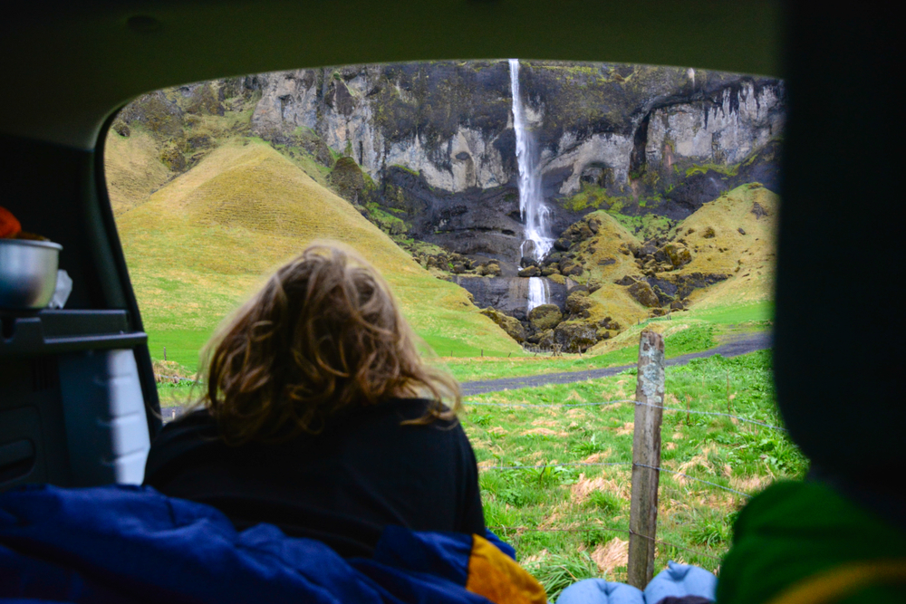A women sitting in the back of a campervan in Iceland, looking out at a waterfall.