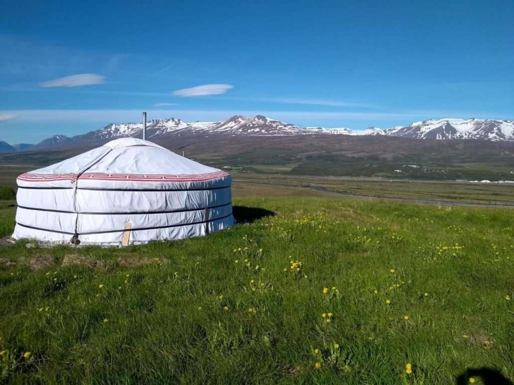 Iceland yurt sits in the open landscape among vast snow capped mountains.