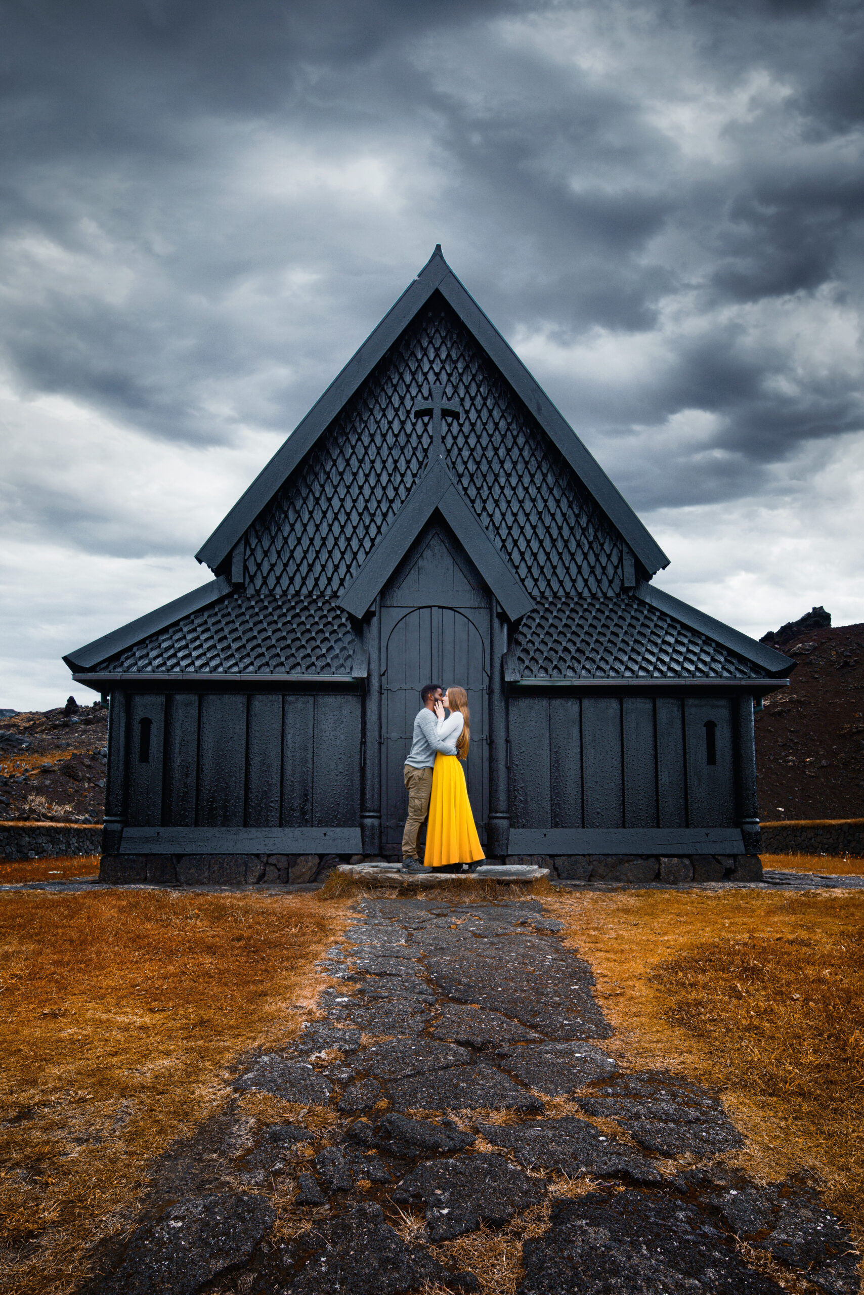 Couple standing and kissing in front of Heimaey Stave Church in Iceland on a moody day
