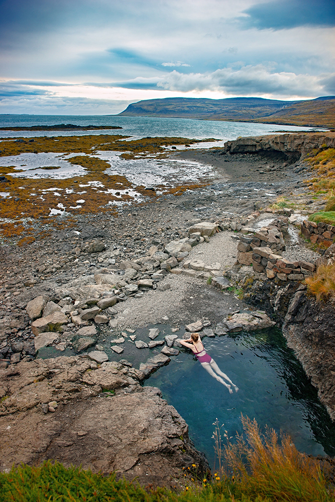 Woman laying in the secret Hellulaug hot spring one of the best Iceland hidden gems