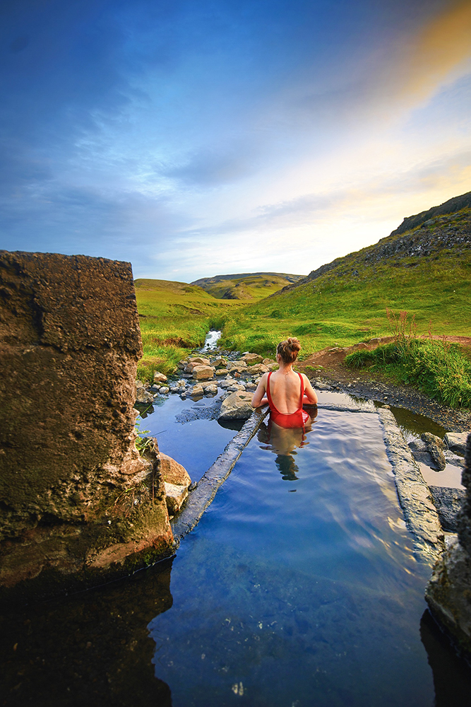 Woman in red bathing suit laying in secret hot spring in Iceland on a sunny evening