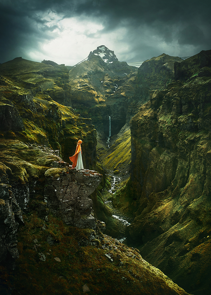 Woman in yellow cape standing in a cliff at Mulagljufur Canyon one of the best hidden gems in iceland