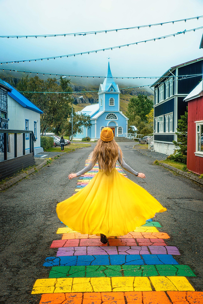 Woman in yellow dress walking in  towards a blue church on a rainbow path one of the best hidden gems in Iceland