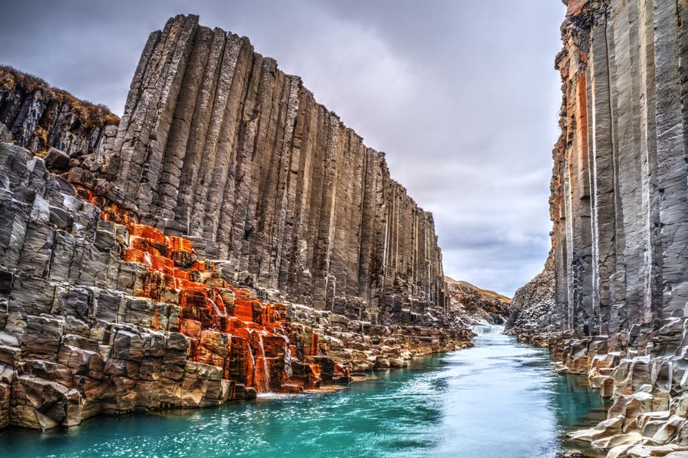 sunset through studlagil basalt canyon one of the hidden gems in Iceland