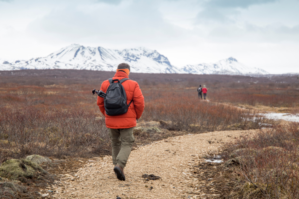 A man hiking the trail to Bruarfoss Waterfall. with mountains in the distance.