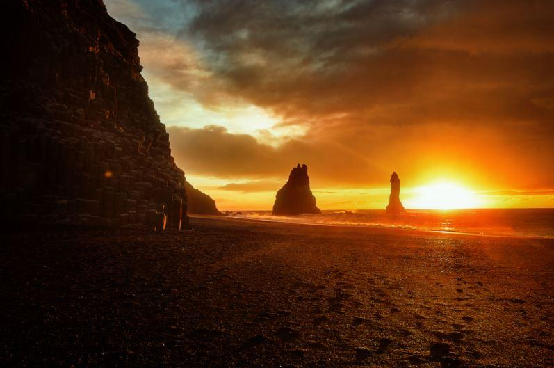sunrise on a black sand beach with basalt rocks on the left and distant sea stacks in the ocean