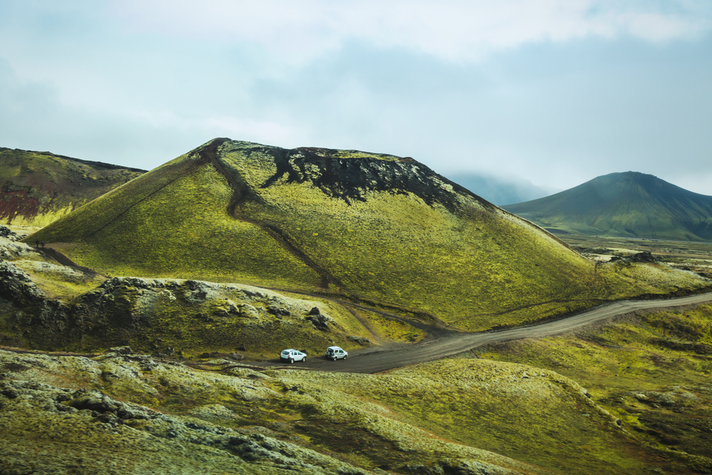 2 white cars driving on a dirt road surrounded by green hills on a moody day in iceland in spring