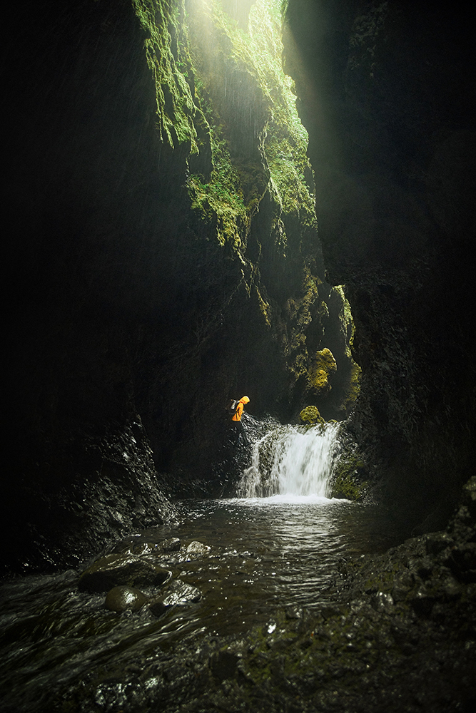Woman in yellow jacket hiking near waterfall in ravine in Iceland with Nauthusagil Waterfall in background