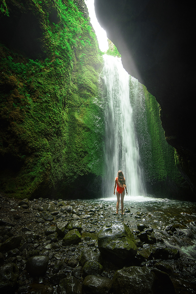 Woman in red bathing suit standing in front of a Waterfall in a cave with Nauthusagil Waterfall in background