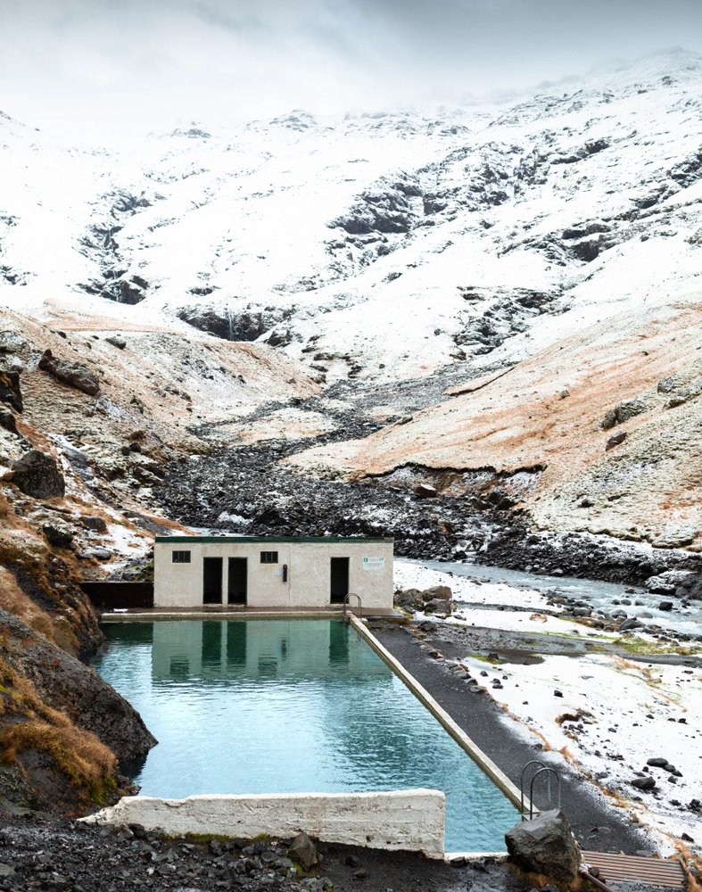 A man made swimming pool hidden in a valley in Iceland. there is snow on the ground, large rocks all around it, and in the distance the slope of a snow covered mountain. At the end of the pool is a small building that is cream with black doors.