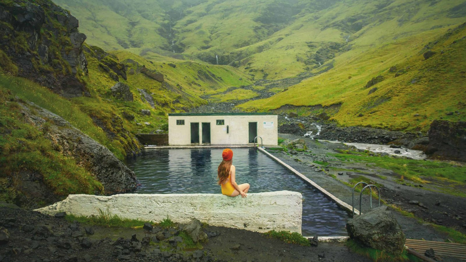 woman in yellow bathing suit sitting on the edge of Seljavallalaug Pool in Iceland