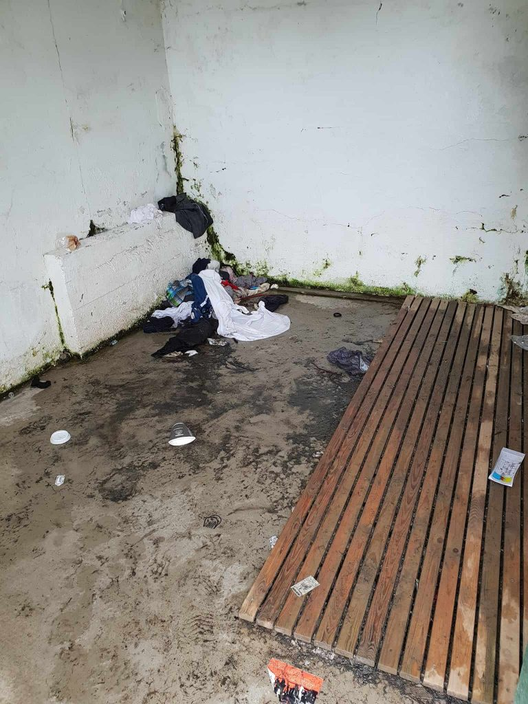 wet nasty clothes and trash in one of the changing rooms at Seljavallalaug pool