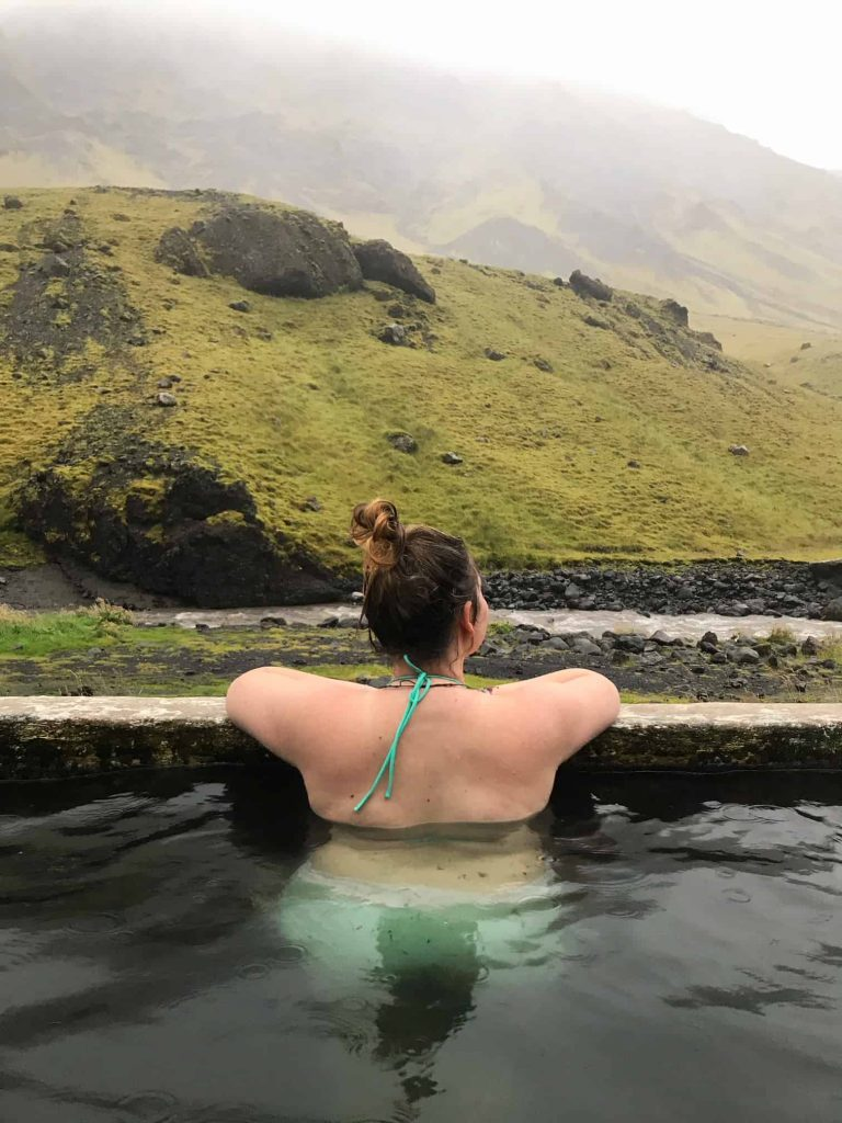woman looking way, chest deep in the water resting with her arms on the sides of Seljavallalaug pool