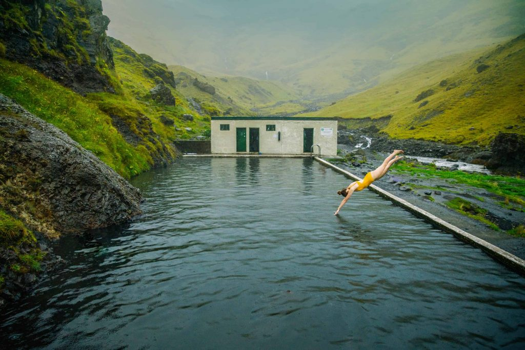 woman in yellow bathing suit diving into Seljavallalaug pool in iceland on a cloudy day