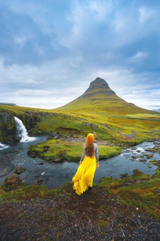 woman standing in a yellow skirt, grey shirt and yellow hat looking at a green mountain in the distance, there is a small waterfall to her left on Snaefellsnes Peninsula