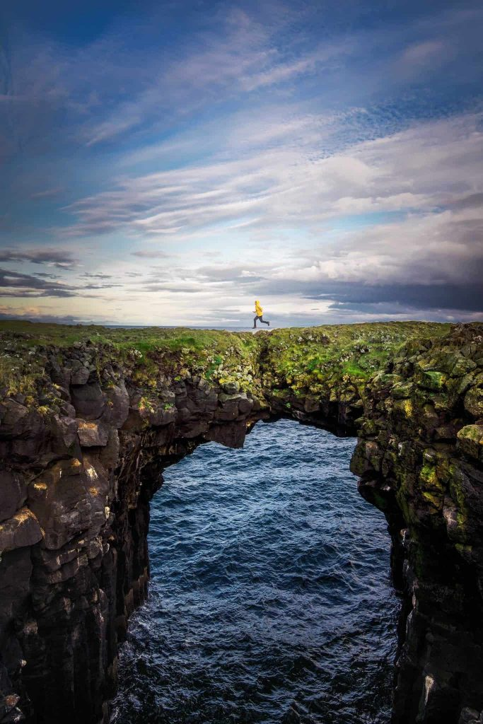 person in a yellow jacket and black pants mid air, jumping on a land bridge overwater on a moody day