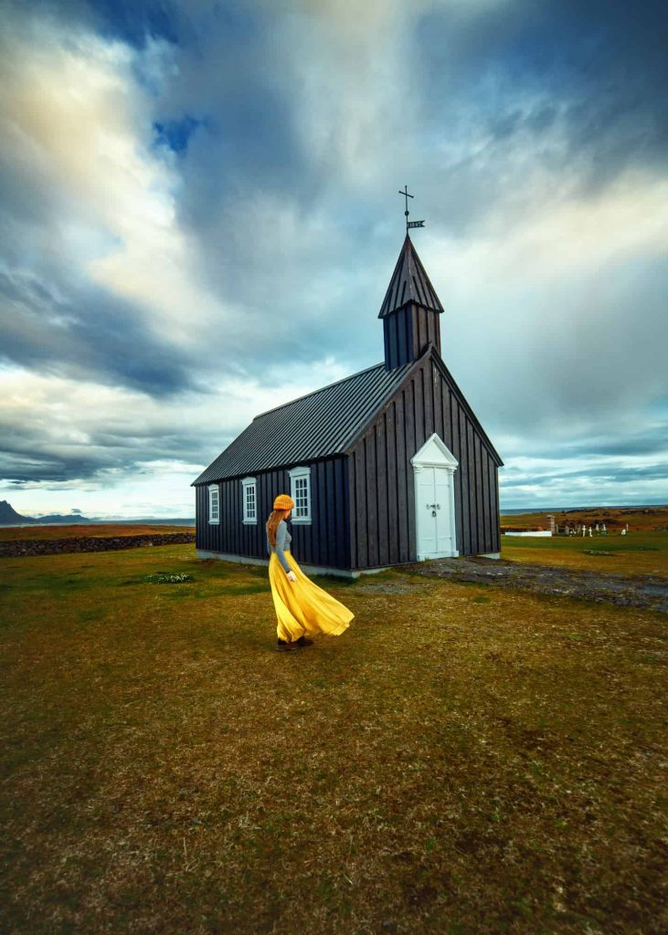 woman standing in a yellow skirt, grey shirt and yellow hat. the wind is blowing her skirt. she is standing in front of a black church with white door on a cloudy day