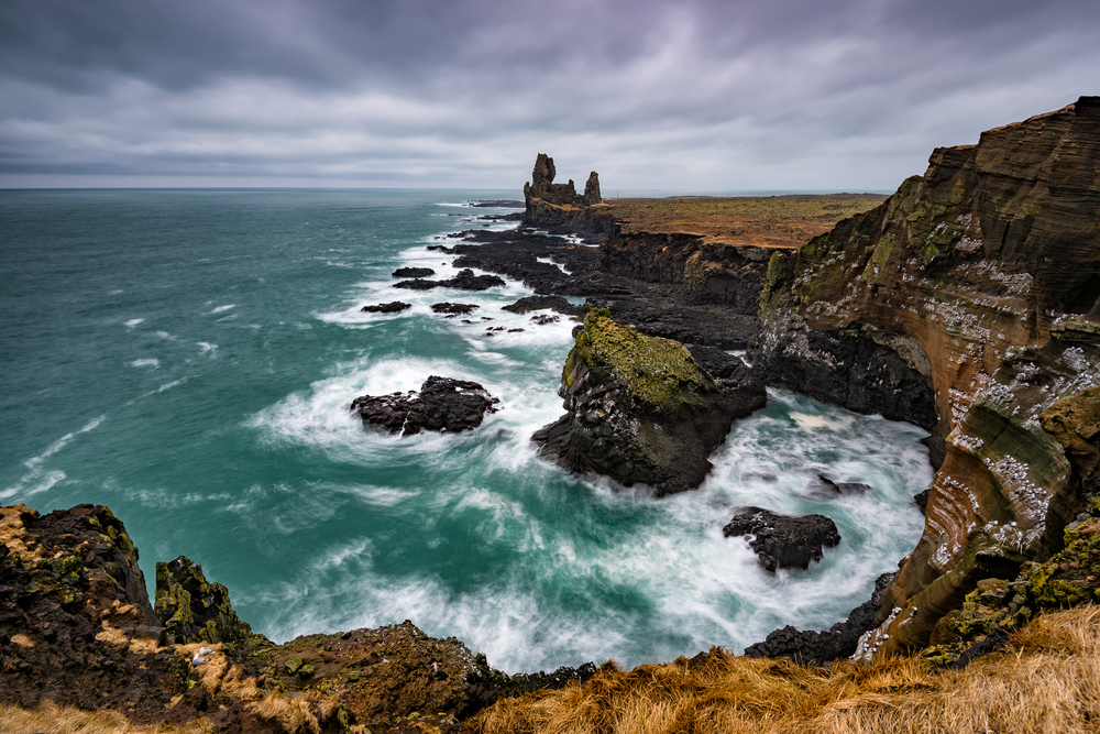 a rugged coastline with rough waves on a cloudy day.