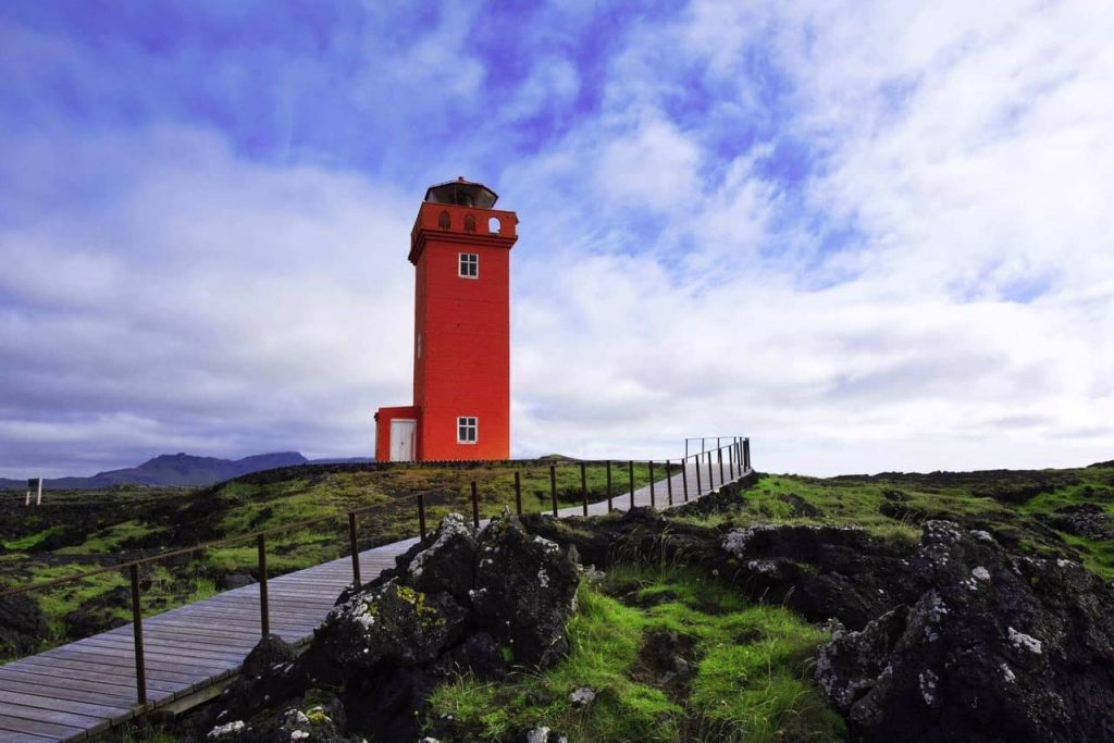 red lighthouse on the coast of iceland on a sunny day