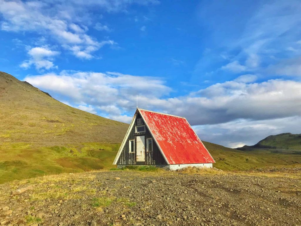 a black hut with a red roof on a rocky hill. It's a sunny day with blue skies