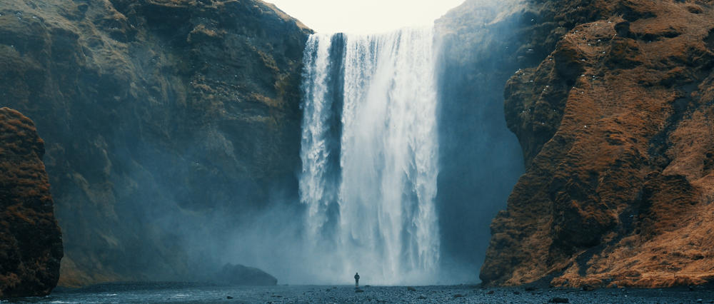 person standing infront of skogafoss waterfall in iceland on a moody day