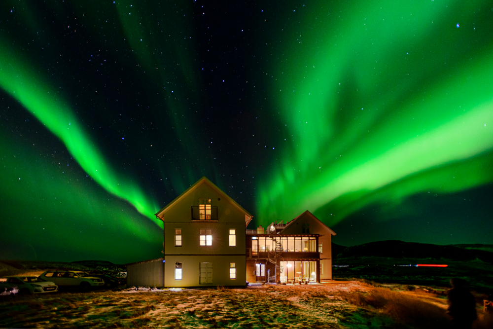 Hotel in iceland lit up at night with northern lights in the sky
