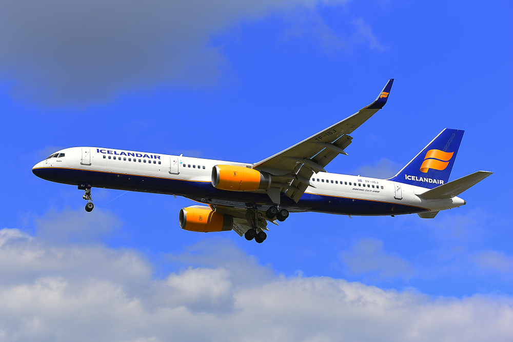 Icelandair airplane flying over head on clear day with blue skies and clouds