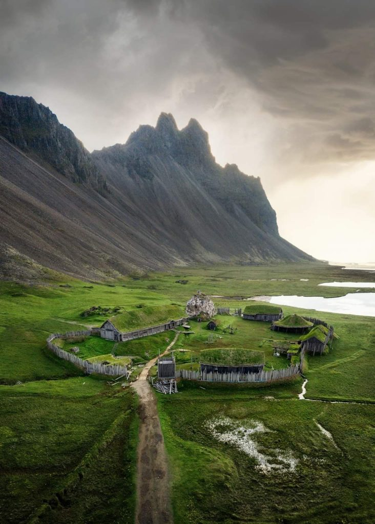 Aerial shot of small fake Viking village with mountains in background one of the best secret places in iceland