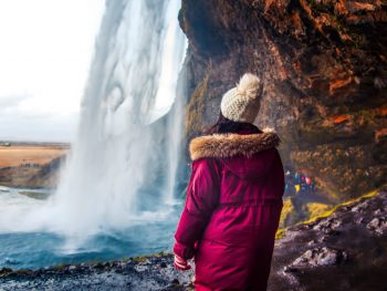 woman wearing a purple coat showing off one of the best jackets for iceland in front of a waterfall