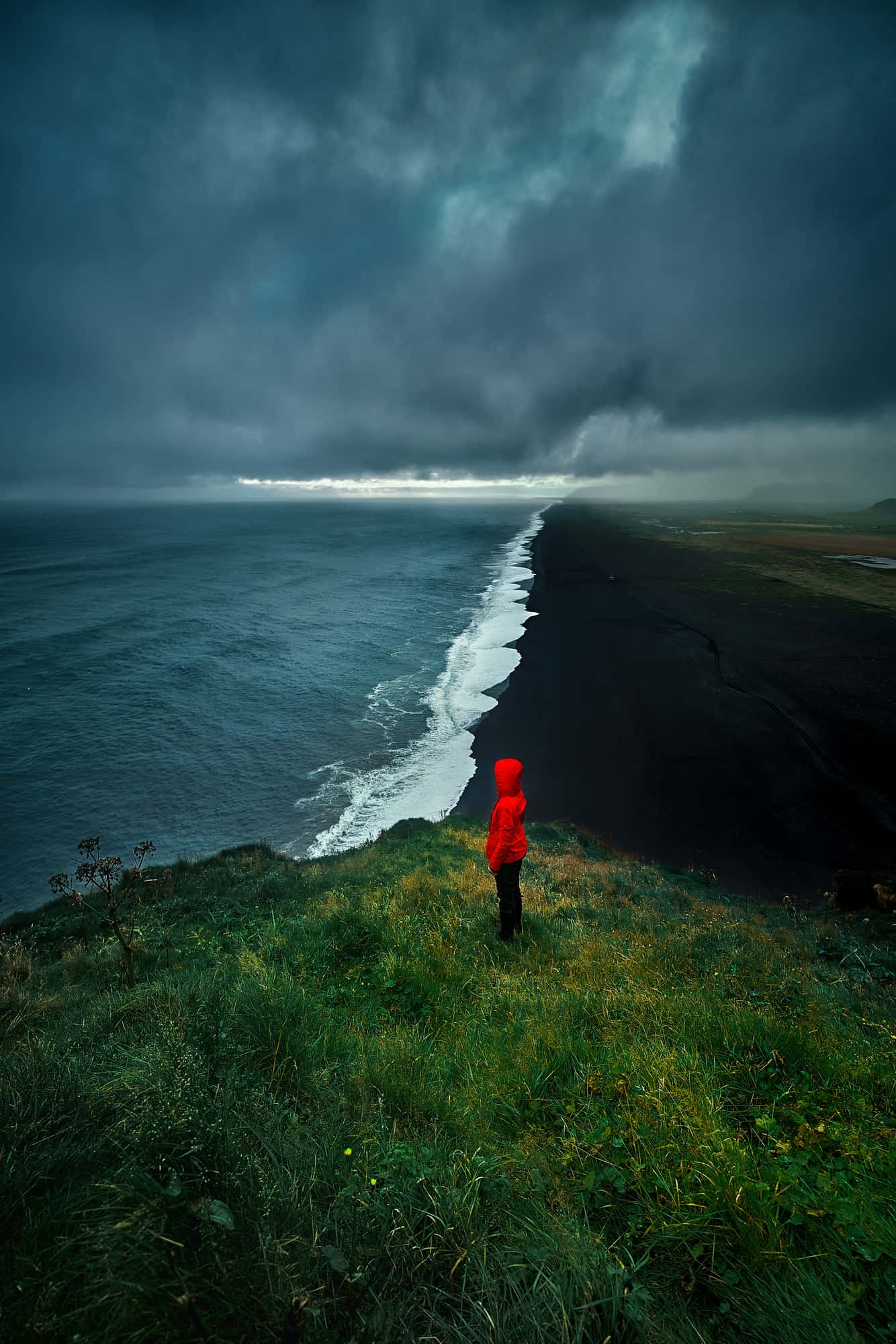 woman in red jacket standing overlooking a black sand beach