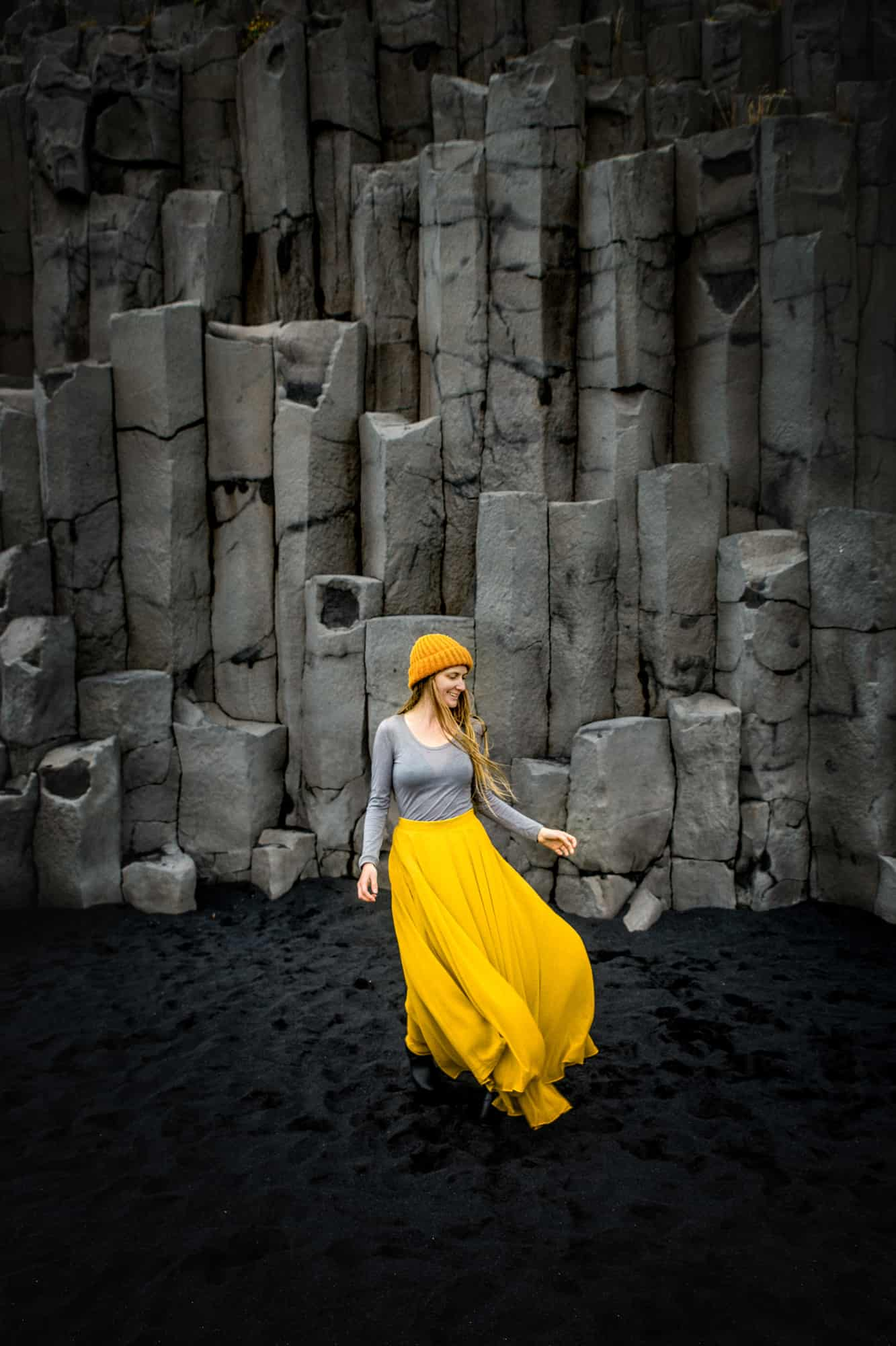 woman standing and smiling in front of basalt rocks on a black sand beach