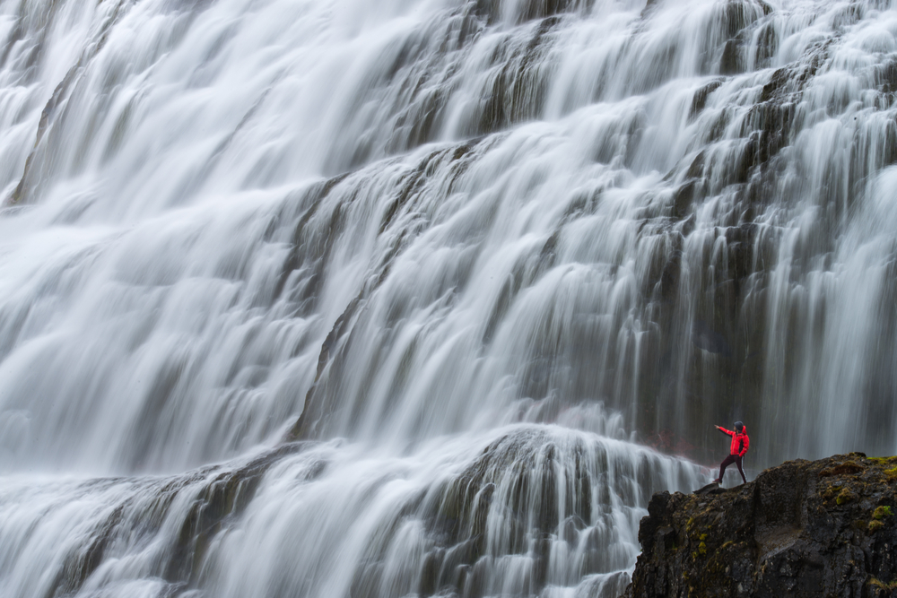 A person in a red coat on the side of a cliff pointing to a massive waterfall. The waterfall takes up most of the picture and is several layers of water cascading over massive rock formations.
