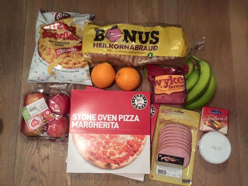 an assortment of groceries, bread, ham, frozen pizza, apples, chips, and fruits on a wood table