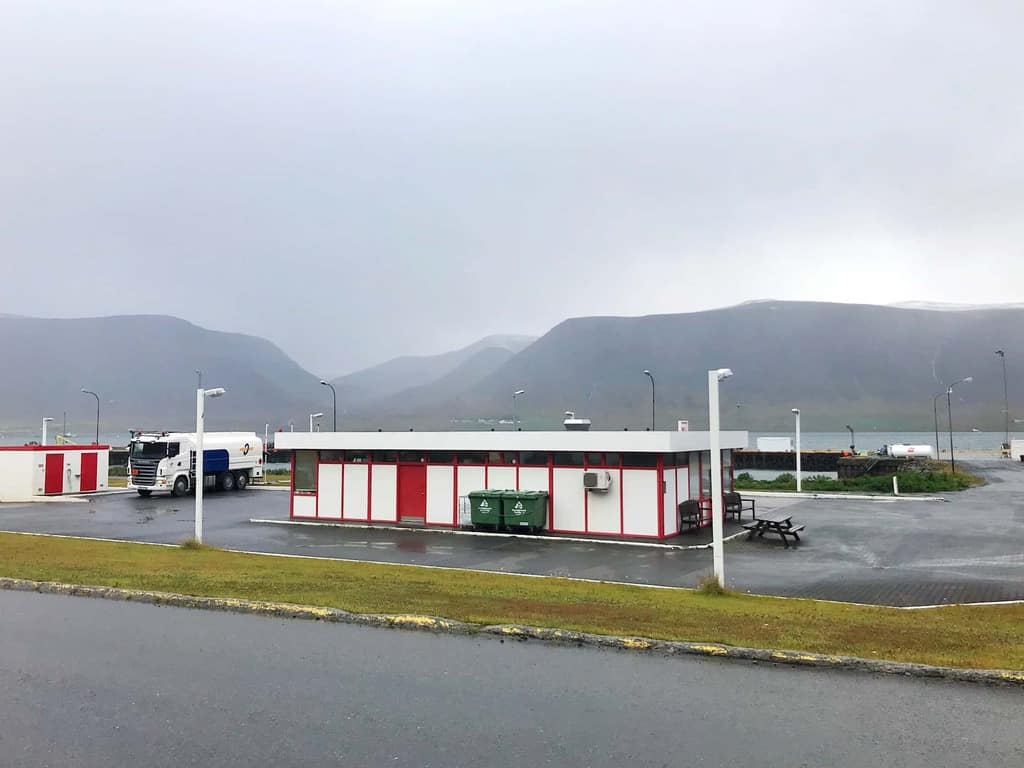 one of the gas stations in iceland on a moody day with clouds the building is red and white