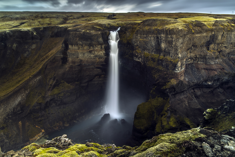 A large waterfall cascading down into a canyon. the canyon is made of dark volcanic rock and there is moss growing on the rocks. The waterfall has a few cascades before it falls directly into the canyon beneath it. One of the best stops on an Iceland road trip.