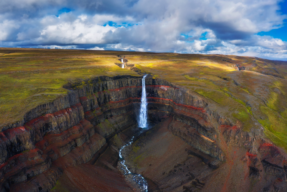 An aerial view of a canyon and field that goes on for miles. You can see waterfalls in the distance and a large waterfall falling into the canyon. It goes straight down the canyon and there are red, brown, and even some orange rocks in the canyon. The sky is blue and cloudy and there is grass in the field. One of the best stops on the Iceland road trip.